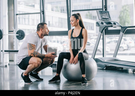 young sportswoman sitting on fitness ball and talking to personal trainer with digital tablet at gym - Stock Photo