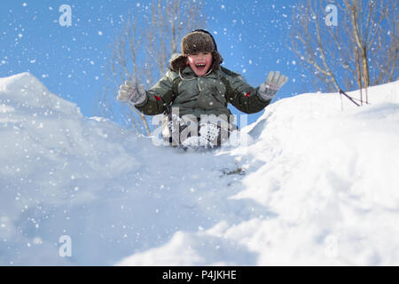 A little boy wearing a hat with a ushanka walks on a snow-covered hill on a winter day.Snowboarding on a sled - Stock Photo