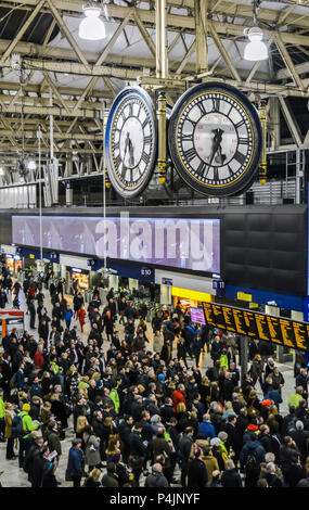 People in front of time board in rush hour at Waterloo train station under large 4-faced clock hanging in the centre of the main concourse. - Stock Photo