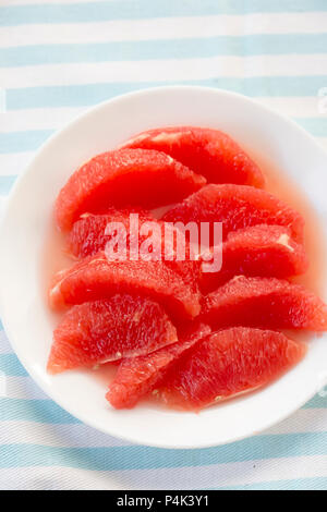 Red grapefruit pieces, segments on white plate - Stock Photo