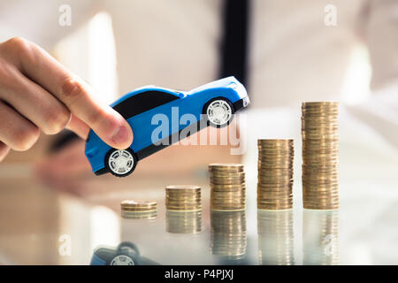 Close-up Of A Person's Hand Holding Car Over Rising Golden Stacked Coins - Stock Photo
