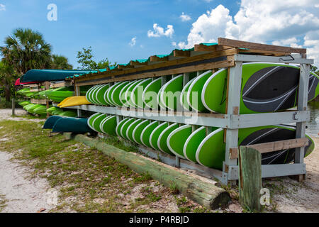 Paddleboards, kayaks and canoes for rent on wooden rack at beach - Dania Beach, Florida, USA - Stock Photo