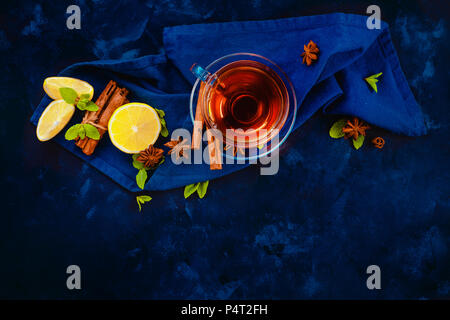 Hot drink header with glass teacup, linen napkin, lemon slices, cinnamon, anise stars and mint leaves on a dark background. Dark food photography flat - Stock Photo