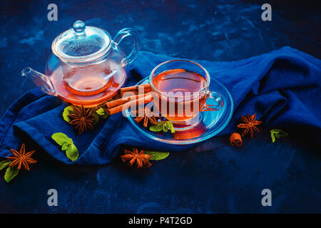 Black tea in a glass cup and a tiny teapot with lemon slices and mint leaves on a dark background. Vibrant colors hot drink header with copy space. - Stock Photo