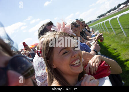 Rowdy crowds cheer on the horses at the side of the racetrack during Royal Ascot cup - Stock Photo