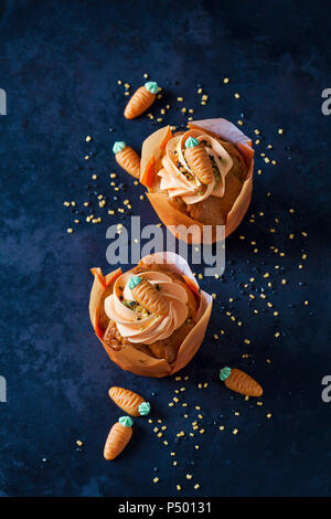 Two carrot cup cakes garnished with  cream topping, sugar granules and marzipan carrots - Stock Photo