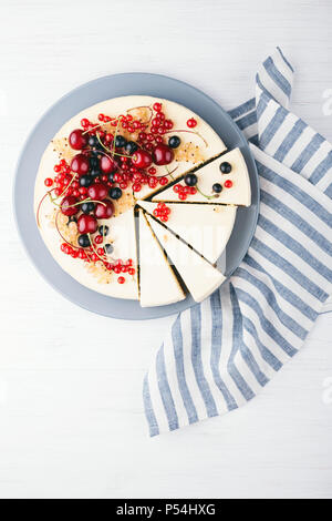 New York cheese cake with berries on white wooden table. Top view. Red currant, black currant and cherry. - Stock Photo