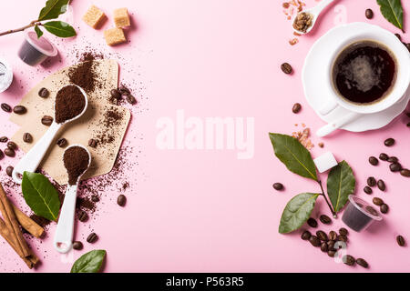 Food background with ground coffee in spoons, coffee beans, espresso cup, ground and capsules, green leaves, copy space, top view. - Stock Photo
