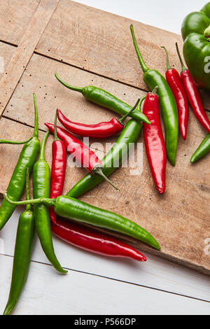 Chili colored peppers for cooking sauce on an old wooden board - Stock Photo