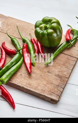 colored hot chili peppers on a wooden board - Stock Photo