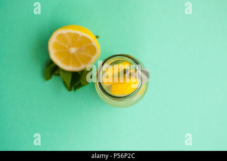 Top view of mason jar glass of lemonade or mojito with lemons and mint on turquoise background. - Stock Photo