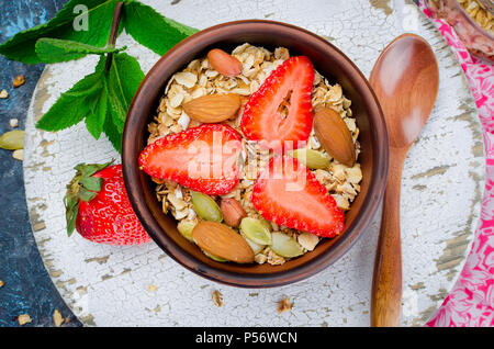 Fresh granola, muesli with strawberries, almonds, peanuts and seeds in a ceramic bowl on a white wooden background, selective focus, toned photo - Stock Photo