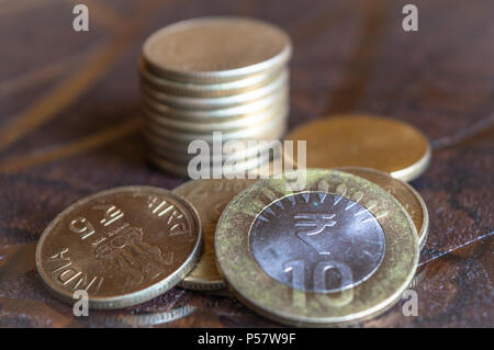 Indian currency Rupees 5 and Rupees 10 coins piled on a table - Stock Photo