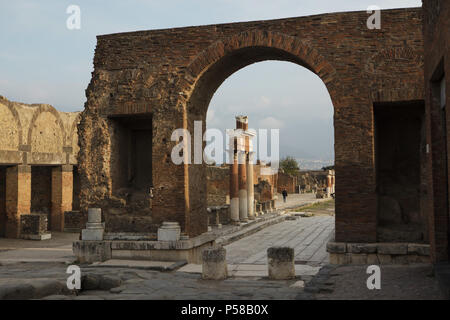 Roman Forum in the archaeological site of Pompeii (Pompei) near Naples, Campania, Italy, pictured through the Roman triumphal arch. - Stock Photo