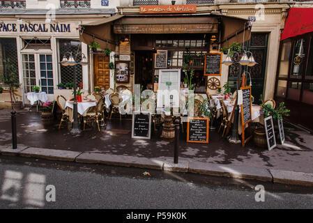 Paris, France - August 13, 2017. Typical french street rue Descartes with La Maison de Verlaine Paris restaurant with summer terrace, outdoor chairs a - Stock Photo