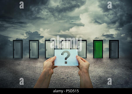 Hands hold a sheet with question mark inside in front of closed doors choosing a different one. Lost people, business confusion concept. Difficult dec - Stock Photo