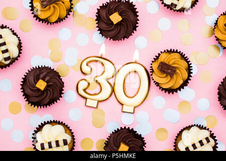 Number 30 gold candle with cupcakes against a pastel pink background - Stock Photo