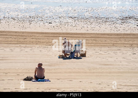 Lyme Regis, Dorset, UK. 27th June 2018. UK Weather. People sit on the beach on deckchairs under hot sun and blue sky. Credit: PQ Images/Alamy. - Stock Photo