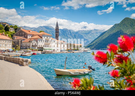 Scenic panorama view of the historic town of Perast at famous Bay of Kotor with blooming flowers on a beautiful sunny day with blue sky and clouds in  - Stock Photo