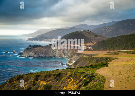Scenic panoramic view of the beautiful coastline of Big Sur with historic Bixby Creek Bridge along world famous Highway 1 with dramatic cloudscape in  - Stock Photo