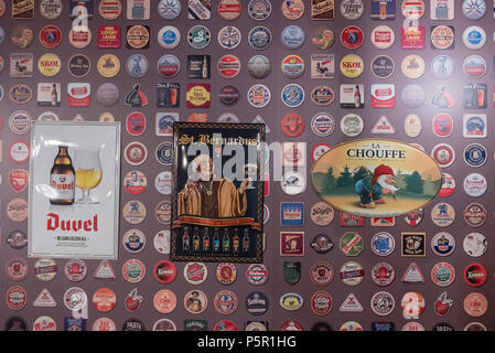 Wall decorated with lots of beer mats from around the world. - Stock Photo