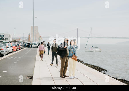 Lisbon, May 1, 2018: A couple of men and women make a selfie on the waterfront in Belem. People are walking around. In the background April 25 The bridge, the sea and the yacht are floating - Stock Photo