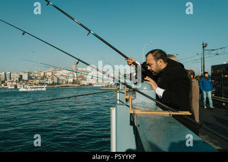 Istanbul, Turkey - January 06, 2018: Local fishermen fishing on Galata Bridge to relax and enjoy their hobby in Istanbul, Turkey. - Stock Photo