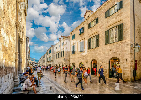 Tourists walk the stradun, main street in the historic walled city of Dubrovnik on a sunny, warm day on the Adriatic coast of Croatia - Stock Photo