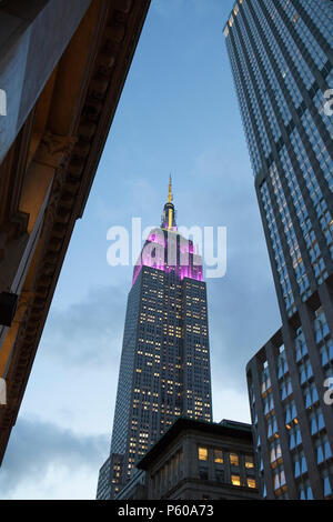 The art-deco architecture of New York's Empire State Building reaches into the dusk sky - Stock Photo