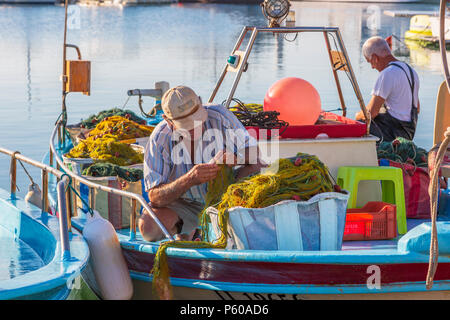 Local fishermen repairing the fishing nets on a traditional styled fishing boat in the old harbour, Ayia Napa, Cyprus - Stock Photo