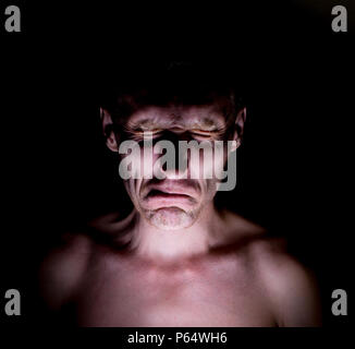 Stylish dark humorous portrait of adult caucasian man who funny wrinkles his face. - Stock Photo