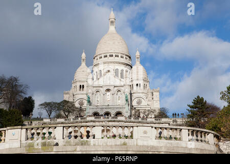The Basilica of the Sacred Heart of Paris, commonly Sacré-Cœur Basilica overlooks the City of Paris and is one of it's major tourist hotspots - Stock Photo