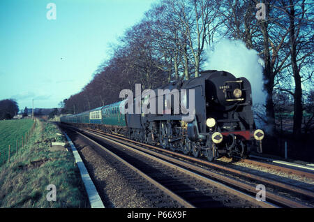 A westbound express near Micheldever headed by Bulleid rebuilt West Country Class Pacific No.34013, Okehampton. - Stock Photo