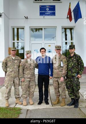 (From left to right) Sgt. Jamie Griffin, MWR Director and Personnel Sgt., and Cpt. Timothy Saccucci, Chaplain, 877th Engineer Battalion, Alabama National Guard; Mr. Dragos Cornateanu, Cincu Primary School Official; Lt. Col. Shawn Arnold, 877th Engineer Battalion Commander, Alabama National Guard, and 1st Lt. Dan Georgescu, Rotation 1 Executive Officer, 3rd Engineer Battalion, Romanian Land Forces, in the front of Cincu Primary School on May 18, 2016 in Cincu, Romania.  Over the next several months, U.S. Army Europe, Alabama Army National Guard and Romanian Land Forces plan to deliver support f - Stock Photo