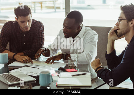 Businessmen discussing work sitting at conference table in office. Two men discussing work while another man is talking on mobile phone. - Stock Photo