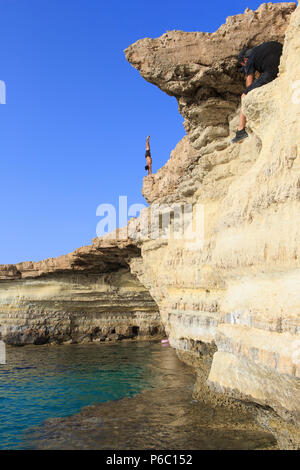 A male diver prepartion to dive from the cliffs into the turquoise water at the Sea Caves near Cape Greco, Cyprus - Stock Photo