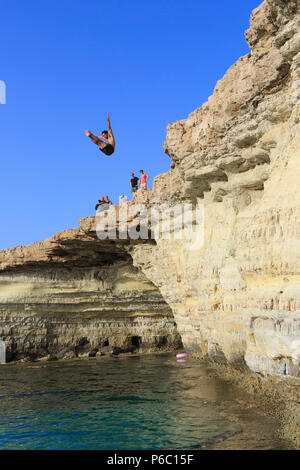 A male diver diving from the cliffs into to the turquoise water at the Sea Caves near Cape Greco, Cyprus - Stock Photo