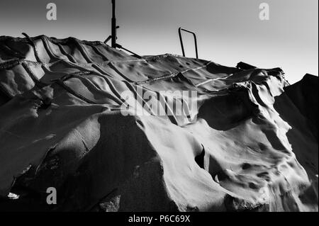 Abstract pattern of a deformed ship hull at the Grindavik ship cemetry covered in an artistic black and white image, iceland april 2018 - Stock Photo