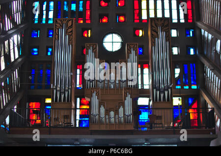 organs on a balcony inside a church colored windows in the back - Stock Photo