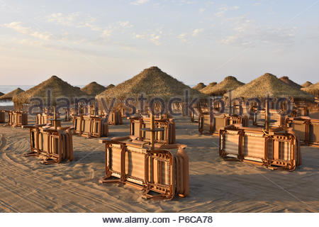 Sunbeds and straw parasols on the beach, early morning in Malaga Andalusia Southern Spain. - Stock Photo