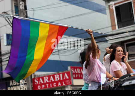 A woman proudly waving the rainbow flag.  Thousands gathered around the Marikina Sports Center, Manila, Philippines for the grand Pride March and Festival 2018. The Metro Manila Pride aims to provide a safe, informed, intersectional, educational and empowering spaces for the gay Filipinos. - Stock Photo