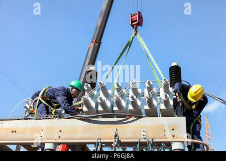 Johannesburg, South Africa, 04/11/2012, Electricians working on high voltage power lines. Highly skilled workmen servicing the electricity gri - Stock Photo
