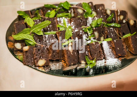 Chocolate brownies with nuts on a tray for catering at gala dinner banquet event - Stock Photo