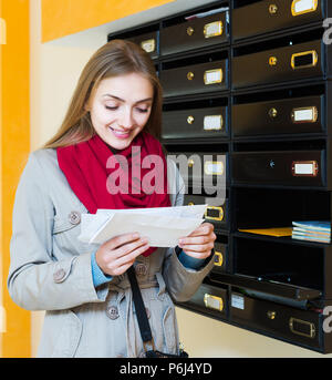 Happy young girl in coat checking correspondence at lobby - Stock Photo