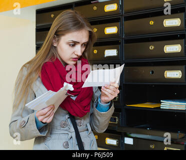 Young woman in coat receiving ugly news by post - Stock Photo
