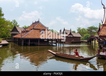Laem Chabang, Thailand -- March 16, 2016. Woman paddles a long-tail boat in Thai water markets. - Stock Photo