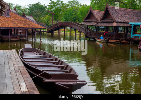 Laem Chabang, Thailand -- March 16, 2016. A boat is tied up at a pier in the water markets; another pulls up to a store. - Stock Photo