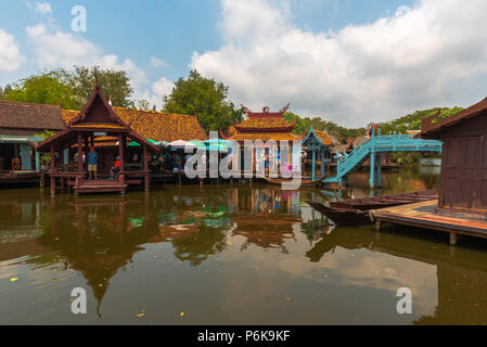 Laem Chabang, Thailand -- March 16, 2016. Tourists explore retail stores built over the water in Thailand. - Stock Photo