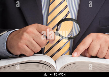 Closeup of businessman holding magnifying glass and looking for information - Stock Photo