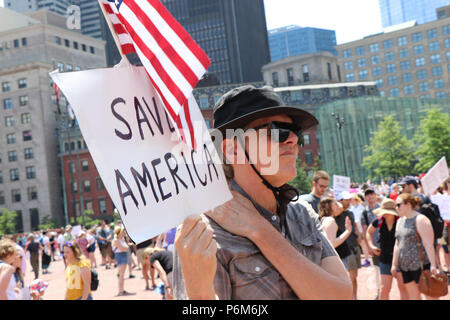 Boston, Massachusetts, USA. 30th June, 2018. IMMIGRATION BOSTON Citizens rally and march against separation of immigrant and migrant families and their children by the government and for the closing of the ICE, the Immigration & Customs Enforcement agency and against President Trump's immigration policies.Approximately 15,000 participants rallied on City Hall Plaza and marched to Boston Common Where more speeches were delivered. Notable speakers were Sen. Elizabeth Warren, Sen. Edward Markey, and Congressman Joe Kennedy III.Along the way a small group of 4 or 5 masked individuals, consid - Stock Photo